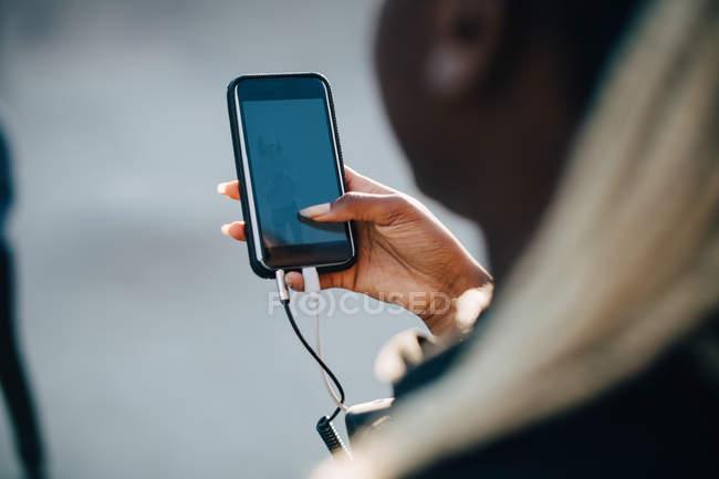 Imagen recortada de una mujer joven escuchando música a través del teléfono inteligente - foto de stock