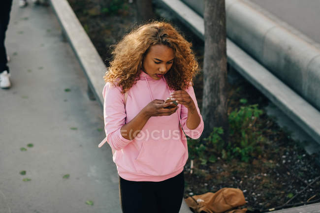 High angle view of woman text messaging on mobile phone at skateboard park — Stock Photo
