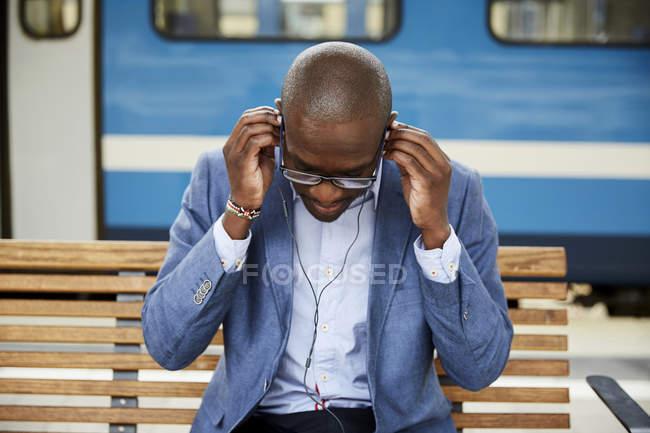 Geschäftsmann stellt Kopfhörer ein, während er am Bahnhof sitzt — Stockfoto