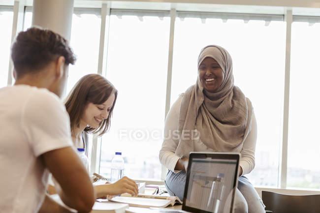 Étudiants d'université de sourire étudiant ensemble dans la salle de classe — Photo de stock