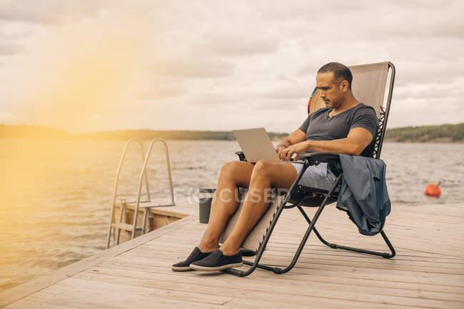 Comprimento total de homem maduro usando laptop enquanto sentado na cadeira de convés no molhe — Fotografia de Stock