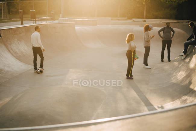 Piena lunghezza di amici multietnici allo skateboard park — Foto stock