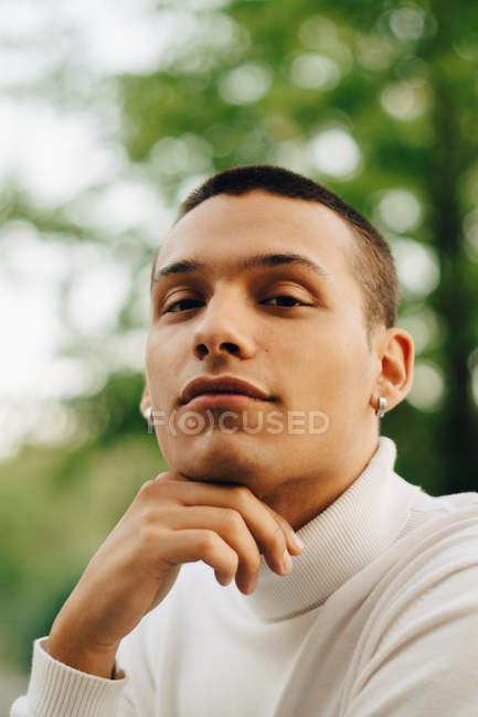 Close-up portrait of young man with hand on chin — Stock Photo