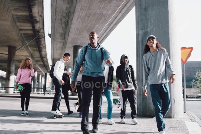 Полная длина друзей, идущих под путепроводом на улице города — стоковое фото