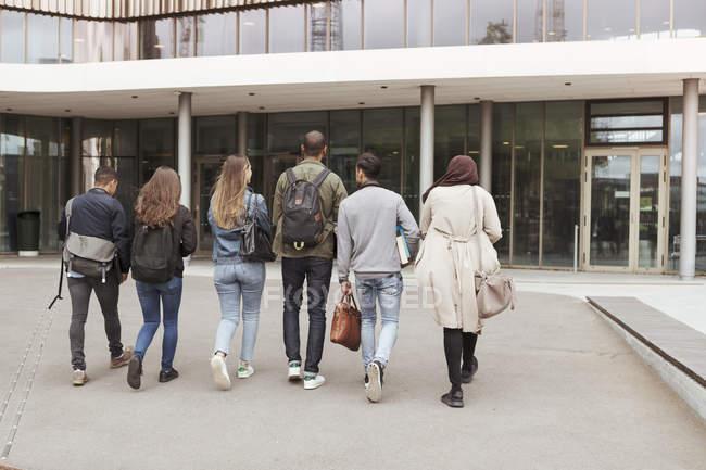 Vista posteriore di studenti multietnici che camminano contro la costruzione nel campus delle scuole superiori — Foto stock