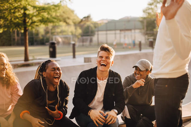 Cheerful multi-ethnic friends talking at skateboard park — Stock Photo