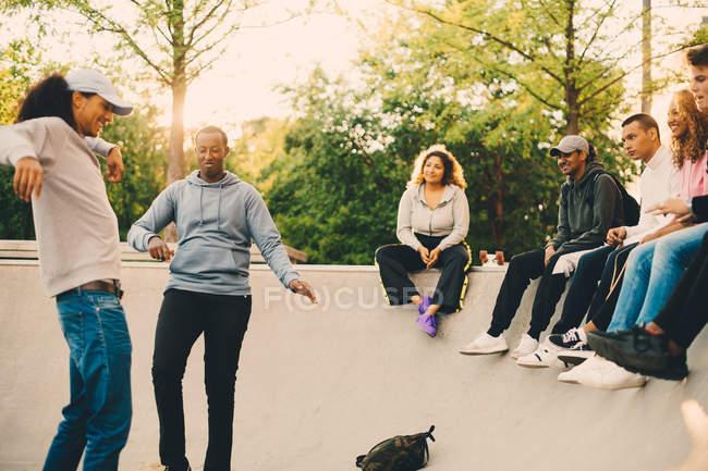 Друзья смотрят на танцующих мужчин в скейтборд-парке — стоковое фото