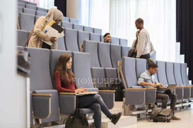 Jóvenes estudiantes que estudian en la sala de conferencias de la universidad - foto de stock