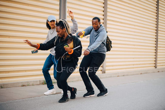 Full length of friends dancing on sidewalk by shutter in city — Stock Photo