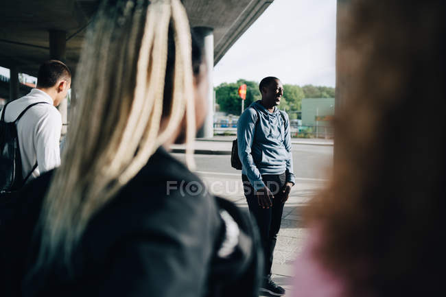 Friends looking at smiling man standing on street in city — Stock Photo
