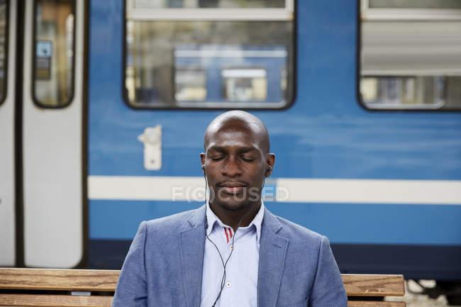 Лысый пригородных слушать музыку, сидя с закрытыми глазами против поезда метро на железнодорожной станции — стоковое фото