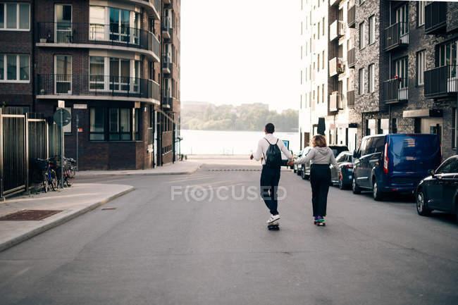 Longitud completa de amigos skateboarding juntos en la carretera en la ciudad - foto de stock