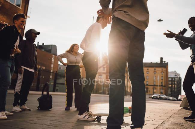 Niedrigwinkel-Ansicht glücklicher Freunde, die Mann beim Skateboardspielen in der Stadt beobachten — Stockfoto