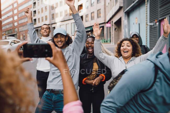 Donna che fotografa allegri amici che ballano sullo smart phone in città — Foto stock