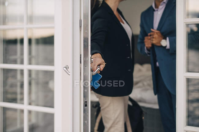 Midsection of mature couple locking glass door at holiday villa — Stock Photo