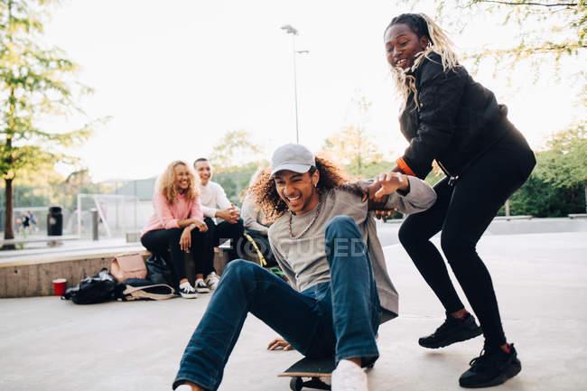 Teenage girl pushing happy man on skateboard while playing at park — Stock Photo