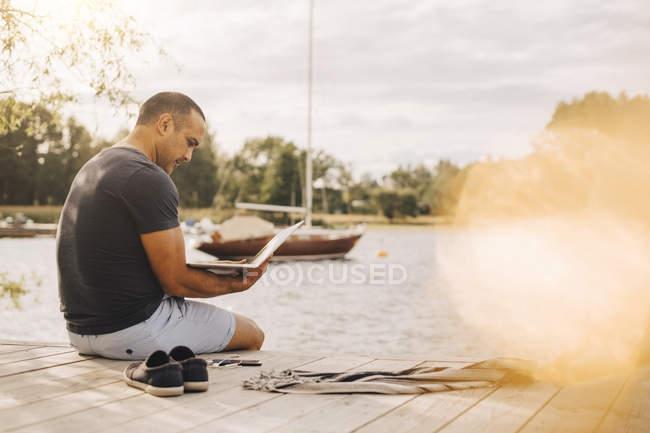 Hombre maduro usando el ordenador portátil mientras está sentado en embarcadero sobre el lago durante las vacaciones - foto de stock