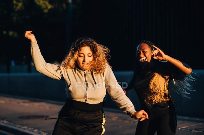 Amici entusiasti che ballano allo skateboard park durante il tramonto — Foto stock