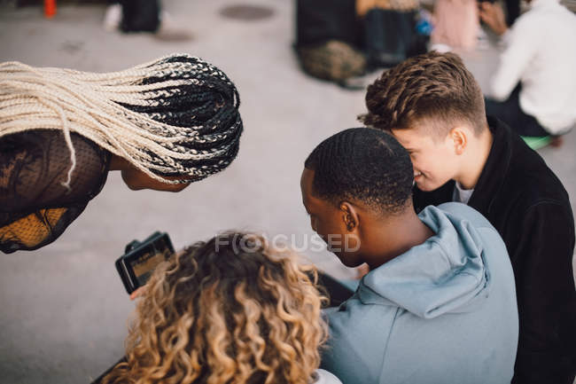 High angle view of multi-ethnic friends watching movie on smart phone at skateboard park — Stock Photo