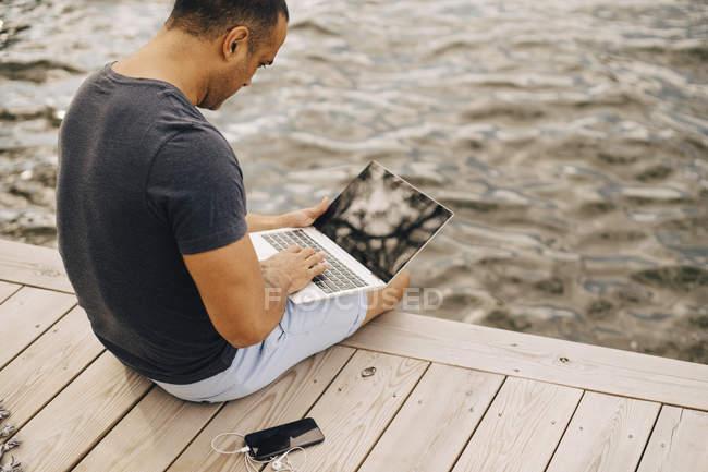 Hombre maduro usando el ordenador portátil mientras está sentado en embarcadero sobre el lago - foto de stock