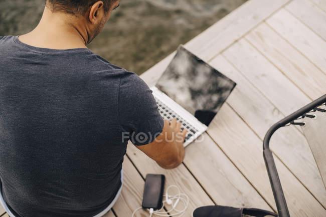 Vista de alto ângulo do homem usando laptop enquanto sentado no molhe — Fotografia de Stock