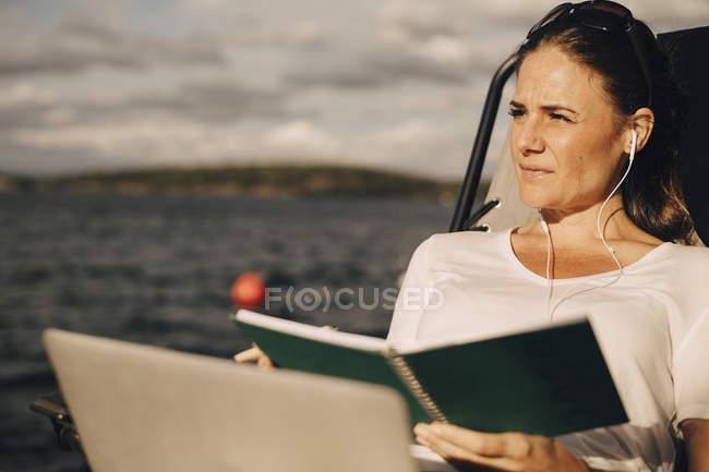 Продуманий жінка з ноутбуком, проведення щоденник дивлячись геть проти озеро — стокове фото