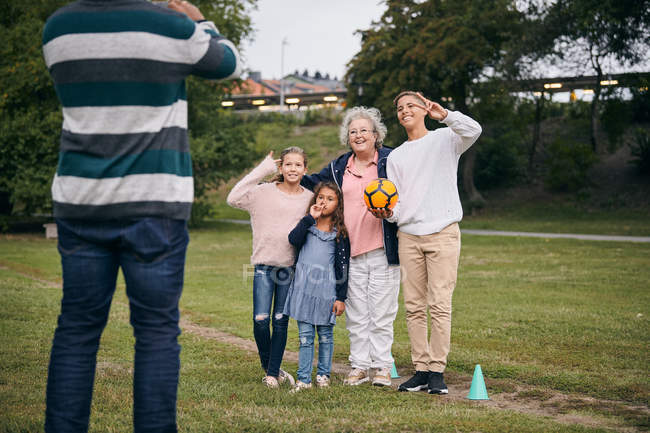 Midsection of man photographing happy grandmother and grandchildren gesturing peace sign in park during picnic — Stock Photo