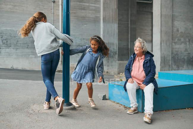 Sorridente nonna guardando le nipotine giocose che girano intorno al palo al parco giochi — Foto stock