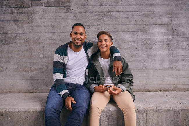 Ritratto di padre e figlio allegro seduto contro il muro — Foto stock