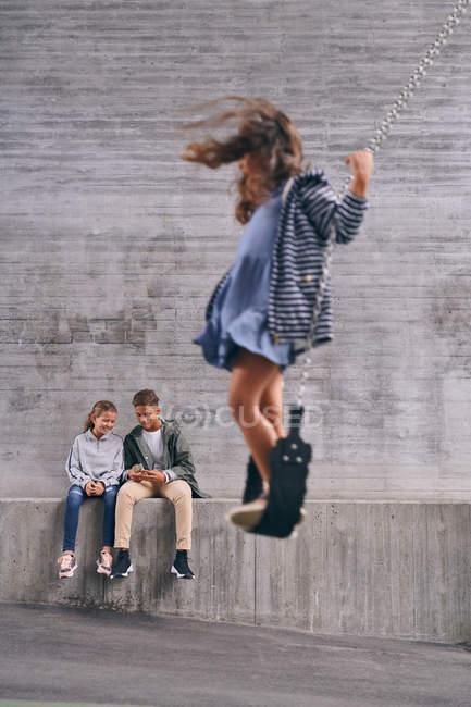 Comprimento total de irmãos usando telefone celular enquanto a menina balançando no balanço no playground — Fotografia de Stock
