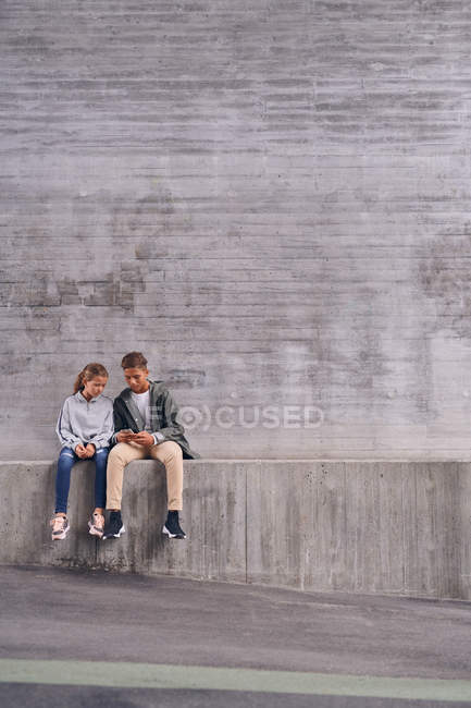 Comprimento total de irmãos usando telefone celular enquanto sentados contra a parede no playground — Fotografia de Stock