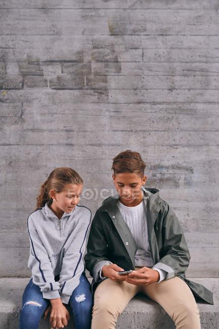 Fratelli che utilizzano il telefono cellulare mentre seduti contro il muro — Foto stock
