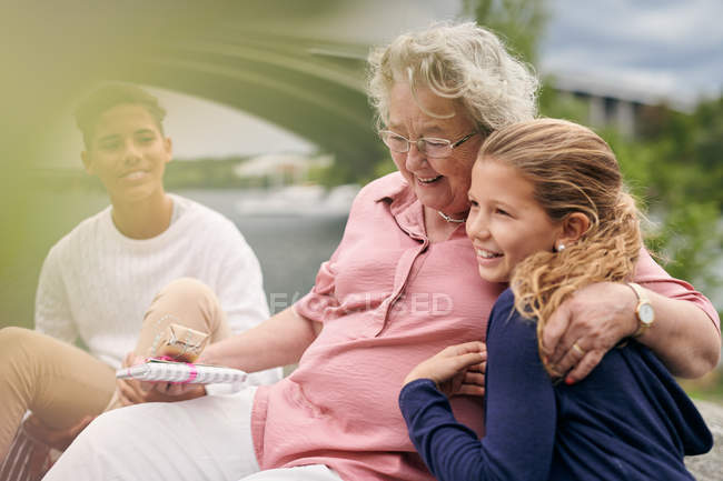 Smiling grandmother holding gifts while embracing granddaughter in park — Stock Photo