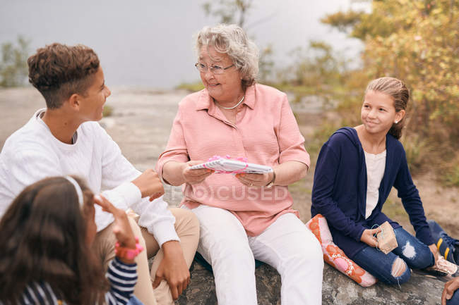 Happy grandmother giving gift to grandson while sitting with granddaughters in park during picnic — Fotografia de Stock