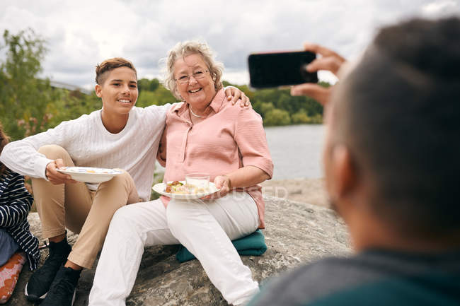 Man photographing grandson and grandmother with meal on rock during picnic — Fotografia de Stock