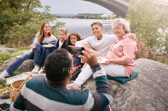 Man photographing happy family with meal on rock in park during picnic - foto de stock