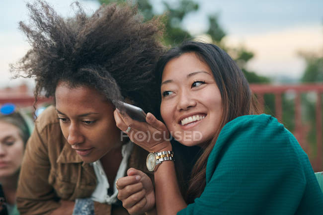 Friends listening mobile phone during social gathering on terrace — Stock Photo