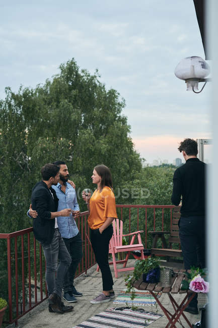 Full length of friends talking while standing on terrace during social gathering — Stock Photo