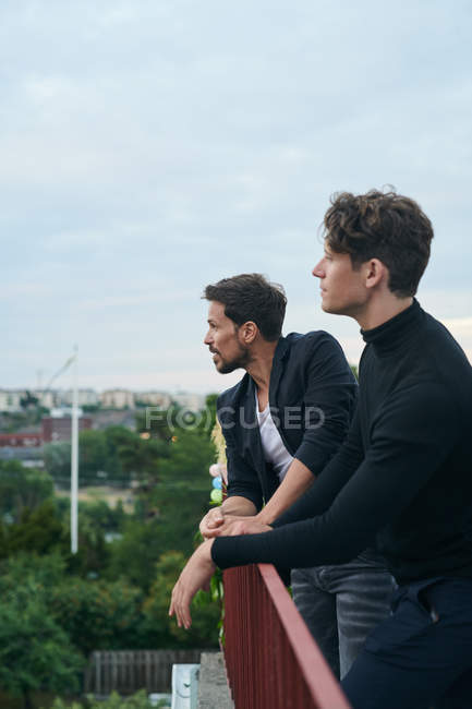 Male friends looking away while standing by railing on terrace against sky — Stock Photo