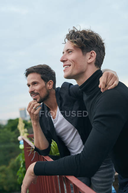 Smiling male friends looking away while standing by railing on terrace against sky — Stock Photo