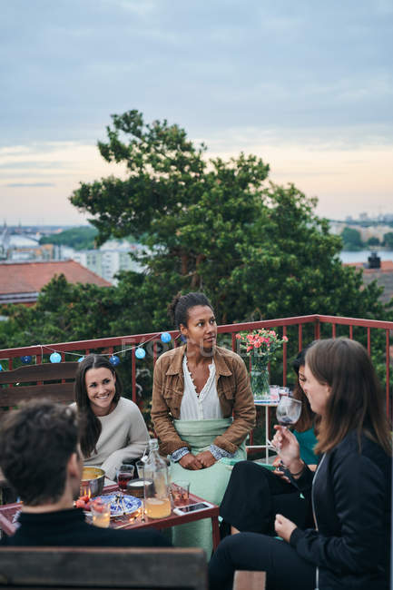 Happy friends enjoying social gathering on terrace during sunset — Stock Photo