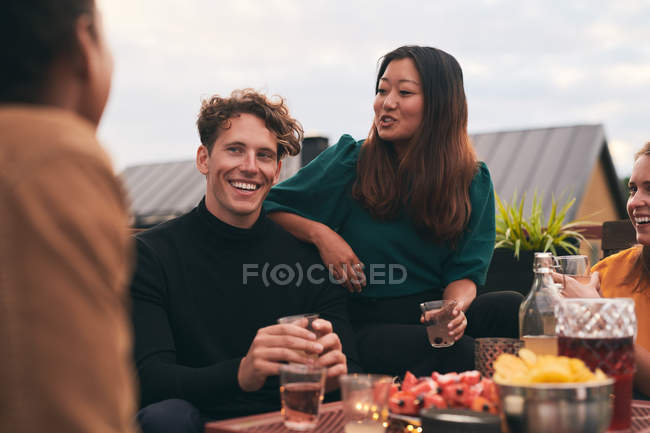 Happy friends talking while having social gathering on terrace — Stock Photo