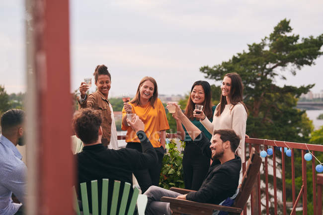 Happy friends toasting drinks on terrace during party — Stock Photo