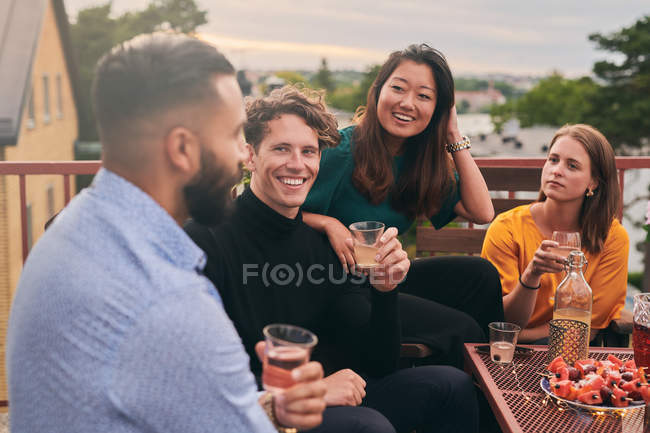 Cheerful friends enjoying social gathering on terrace during sunset — Stock Photo
