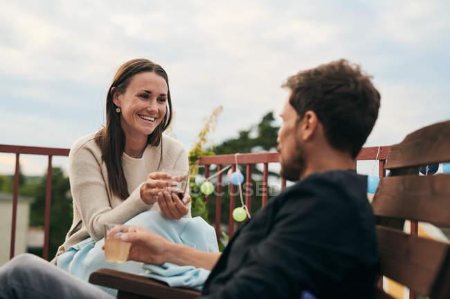 Donna allegra che parla con un amico maschio mentre tiene da bere sulla terrazza durante la raccolta sociale — Foto stock