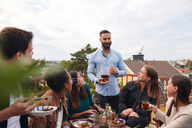 Man talking with friends while holding drink on terrace — Stock Photo