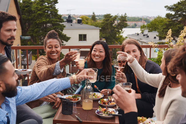 Happy friends toasting drinks while sitting on terrace — Stock Photo