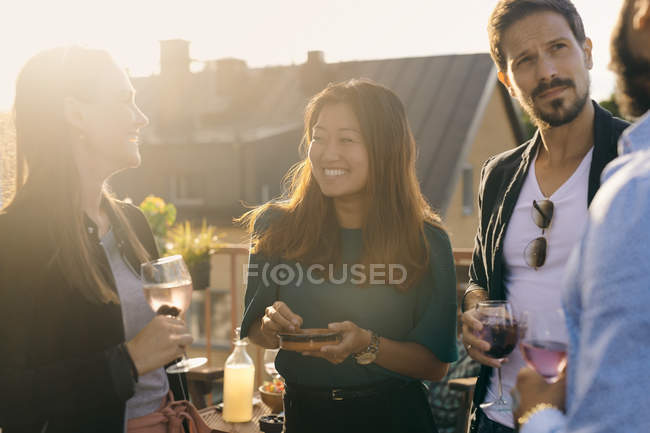 Cheerful friends having social gathering on terrace during sunset — Stock Photo