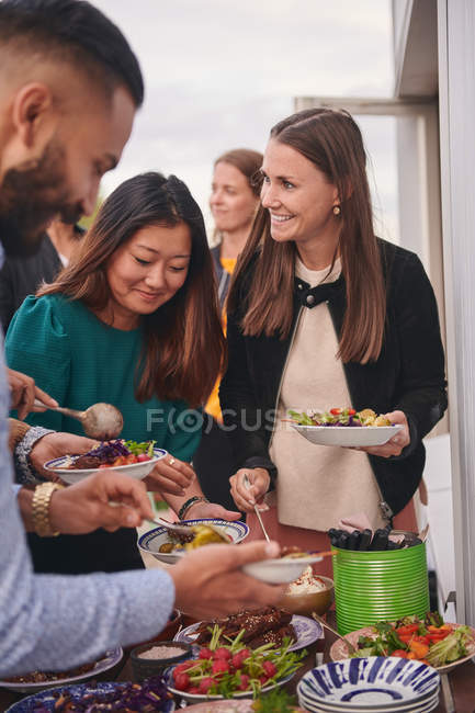 Friends enjoying buffet on terrace — Stock Photo
