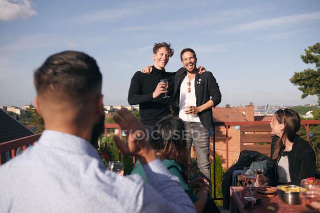 Веселые друзья-мужчины поют во время светового схода на террасе — стоковое фото